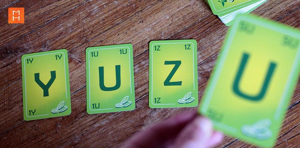 Jeu Yuzu de cartes à lettres mot yuzu sur sol illustrations par Margot Huguet et inventé de Christophe Duveau