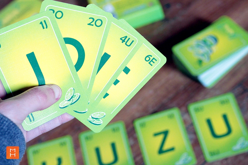Jeu Yuzu de cartes à lettres mise en scène d'une partie avec main qui tient les cartes illustrations par Margot Huguet et inventé de Christophe Duveau